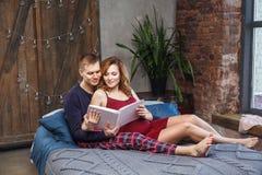 Le portrait de la jeune famille heureuse ont un repos dans la chambre à coucher, dans l'album de participation de vêtements de nu image libre de droits