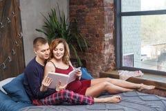 Le portrait de la jeune famille heureuse ont un repos dans la chambre ? coucher, dans l'album de participation de v?tements de nu photographie stock libre de droits