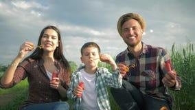 Le portrait de la jeune famille jouant avec des bulles de savon dehors, l'enfant avec la maman et le papa dans des chemises ? car clips vidéos