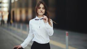 Le portrait de la jeune femme attirante souriant et enlève des lunettes de soleil fraîches banque de vidéos