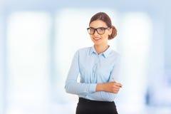 Le portrait de la jeune femme d'affaires gaie de sourire heureuse dans les verres et l'habillement bleu, avec le stylo dans des b Photographie stock