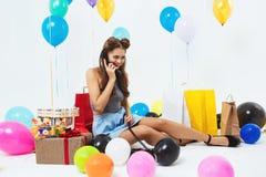 Le portrait de la jeune femme heureuse parlant au téléphone, recevant souhaite Photos stock