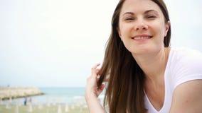 Le portrait de la jeune femme se reposent sur la plage Vent de la mer Méditerranée soufflant ses cheveux dans le mouvement lent clips vidéos