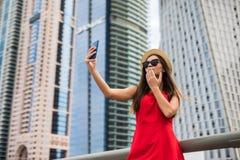 Le portrait de la jeune femme de sourire dans la robe rouge, les lunettes de soleil et le chapeau d'été font le selfie ou le bais image libre de droits
