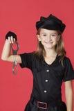 Le portrait de la jeune fille dans la participation de costume de police menotte sur le fond rouge Photographie stock libre de droits