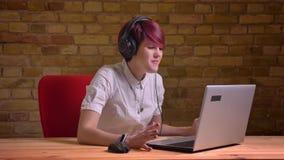 Le portrait de la jeune flamme femelle aux cheveux courts dans des écouteurs devient extrêmement heureux bricken dessus le fond d banque de vidéos