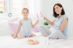 Le portrait de la jeune mère heureuse et de ses petits verres de prise de fille de lait de poule, prennent le petit déjeuner dans photographie stock