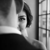 le portrait de la jeune mariée de Moitié-visage au-dessus de l'épaule de l'homme Images stock
