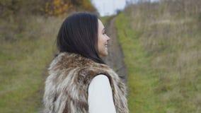 Le portrait de la jolie brune marche à la forêt et regarde l'appareil-photo clips vidéos