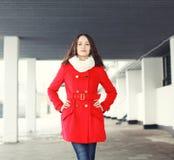 Le portrait de la jolie jeune femme a habillé un manteau rouge dehors Photo stock