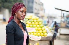 Le portrait de la jolie jeune femme tenant le fruit proche rayonne photo stock