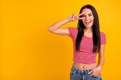 Le portrait de la jolie jeunesse adorable douce font des v-signes que le rire ont le ressort de temps libre elle son moderne d'is photo stock