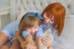 Le portrait de la mère étreint sa petite fille sur un lit pendant le matin Images libres de droits