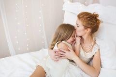 Le portrait de la mère embrasse sa petite fille sur un lit Photographie stock libre de droits