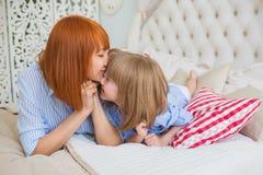 Le portrait de la mère embrassent sa petite fille sur un lit Images libres de droits