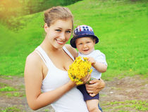 Le portrait de la mère et du bébé heureux avec le pissenlit jaune fleurit Images libres de droits