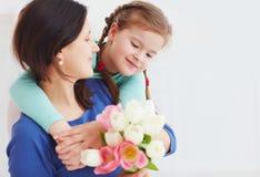Le portrait de la mère heureuse et la fille avec le ressort fleurissent le bouquet images stock
