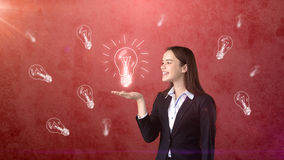 Le portrait de la participation de jeune femme a peint la lampe à lueur sur la paume ouverte de main, fond dessiné de studio Conc Images stock