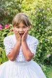 Le portrait de la petite fille étonnée dans la demoiselle d'honneur blanche vêtx Photographie stock
