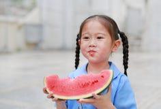 Le portrait de la petite fille asiatique d'enfant dans l'uniforme scolaire ont plaisir à manger la pastèque savoureuse images stock