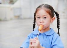 Le portrait de la petite fille asiatique d'enfant dans l'uniforme scolaire ont plaisir à manger la saucisse savoureuse photos stock