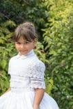 Le portrait de la petite fille de sourire dans la demoiselle d'honneur blanche vêtx Images libres de droits
