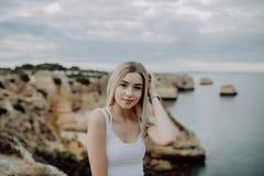 Le portrait de la pose blonde attrayante de femme utilise le chapeau de paille sur la plage rocheuse sur le fond de coucher du so image stock