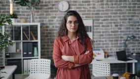 Le portrait de la position sérieuse de jeune femme dans le bureau seul avec des bras a croisé banque de vidéos