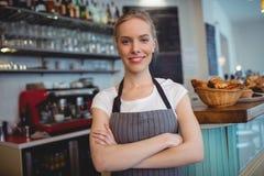 Le portrait de la serveuse heureuse avec des bras a croisé au café Photos stock