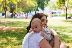 Le portrait de la tête de repos de beau bébé sur le bras de mère, jeune maman s'inquiète son nourrisson en rotant la position apr photos libres de droits