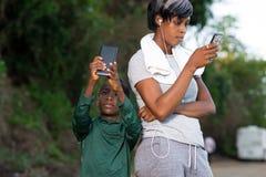 Le portrait de m?re et de fils utilise le t?l?phone portable dehors photos libres de droits