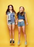 Le portrait de mode de vie de deux meilleurs amis de jeunes filles sautent par-dessus le YE Photos stock