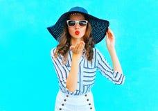 Le portrait de mode que la jolie femme dans le chapeau d'été de paille est envoie un baiser d'air au-dessus de bleu coloré Photo libre de droits