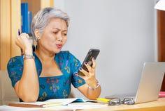 Le portrait de mode de vie de bureau du milieu inqui?t? et soumis ? une contrainte attrayant a vieilli la femme asiatique ? l'aid image libre de droits