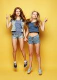 Le portrait de mode de vie de deux meilleurs amis de jeunes filles sautent par-dessus le YE Images stock