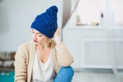 Le portrait de plan rapproché d'une belle dame dans le bleu a tricoté le chapeau Photographie stock