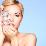 Le portrait de plan rapproché de la belle jeune femme applique la glace au fac Photographie stock