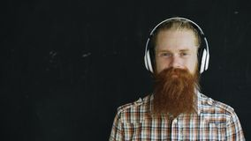 Le portrait de plan rapproché du jeune homme barbu dans des écouteurs écoutent la musique et le regard dans le sourire d'appareil photographie stock libre de droits
