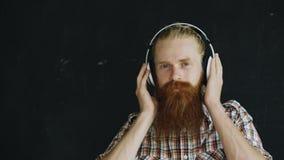 Le portrait de plan rapproché du jeune homme barbu dans des écouteurs écoutent la musique et le regard dans le sourire d'appareil photo stock