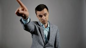 Le portrait de plan rapproché du jeune homme d'affaires est fâché et dirigeant le doigt à la sortie clips vidéos