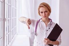 Le portrait de plan rapproché, femme de docteur, donnant manie maladroitement en bas du geste photos libres de droits