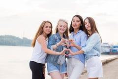Le portrait de quatre jeunes filles d'étudiant montrant le doigt font des gestes le coeur photographie stock libre de droits