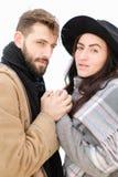 Le portrait de réjouissent l'écharpe et le chapeau de port de couples à l'arrière-plan blanc Images stock
