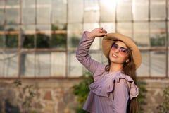 Le portrait de ressort du modèle heureux de brune utilise le chapeau et les lunettes de soleil, appréciant le temps chaud L'espac photo stock