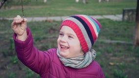 Le portrait de sourire mignon d'années de la fille 3-4 tient une branche d'un arbre Première source Mouvement lent clips vidéos