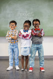 Le portrait de trois enfants d'école se tenant avec des bras a croisé contre le tableau photographie stock libre de droits