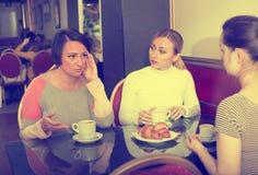 Le portrait de trois a inquiété la femme s'asseyant dans le café Images stock
