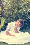 Le portrait de vintage de la petite fille dans la demoiselle d'honneur blanche vêtx Image stock
