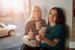 Le portrait de vue de face de deux amis drôles avec des pouces se lèvent et regardant à l'appareil-photo Image libre de droits