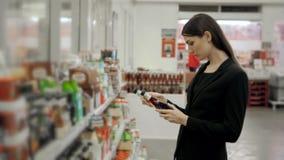 Le portrait des achats positifs de fille de femme conservent la sauce tomate ou le vinaigre balsamique de piments chauds dans l'é Image stock